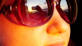 关闭看法少妇在太阳镜的` s面孔,站立在窗口,并且拿着智能手机拍在日落的照片  影视素材