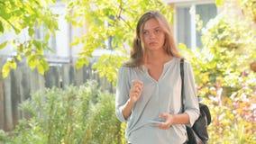 关闭看照相机的俏丽的女孩画象在晴天有被弄脏的绿色叶子背景户外 股票视频