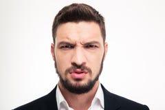 关闭看照相机的恼怒的被激怒的有胡子的商人 免版税库存照片
