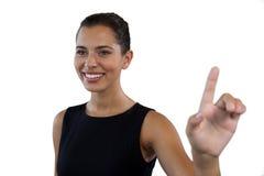 关闭看起来愉快的女实业家去,当接触无形的接口时 库存照片