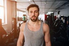 关闭看起来的stong和的俊男站立在健身房和直接 他有一些休息在艰苦以后 免版税库存照片