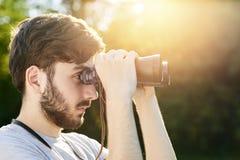 关闭看通过双筒望远镜的年轻有胡子的远足者画象,当有步行设法的森林看某事interestin时 免版税图库摄影