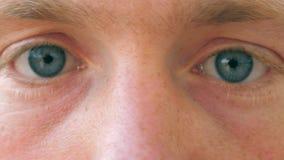 关闭眨眼睛和调查照相机的哀伤的男性蓝眼睛与白天 画象年轻英俊人观看 股票录像