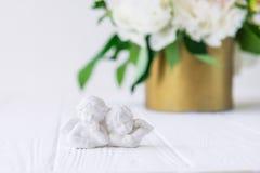关闭石膏的两个古色古香的矮小的可爱的天使小雕象在白色木桌上的与白色牡丹花束在vi的 免版税库存照片