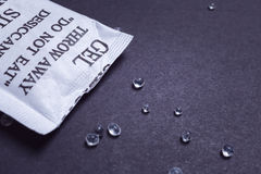 关闭矽土凝胶或干燥剂在纸袋在黑backgroun 库存图片