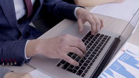 关闭研究膝上型计算机的男性手在有女性同事的办公室,慢动作 股票视频