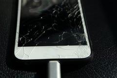 关闭破裂的智能手机屏幕放置在黑皮革 图库摄影