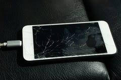 关闭破裂的智能手机屏幕放置在黑皮革 免版税库存图片