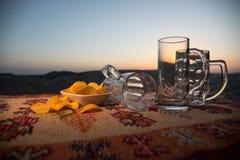 关闭空的杯子在日出背景的啤酒与山 啤酒党在概念 免版税库存照片