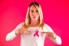 关闭穿一件白色女衬衫的一名美丽的妇女指向一条桃红色乳腺癌了悟丝带用她的手 图库摄影