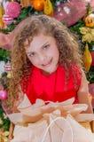 关闭穿一件红色女衬衫和拿着一件礼物在她的手上的微笑的美丽的卷曲女孩,有圣诞树的 免版税库存照片