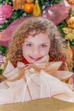 关闭穿一件红色女衬衫和拿着一件礼物在她的手上的微笑的美丽的卷曲女孩,有圣诞树的 免版税库存图片