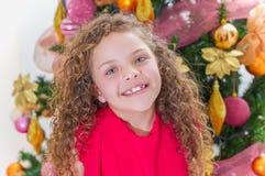 关闭穿一件红色女衬衫和摆在为与后边圣诞树的照相机的微笑的美丽的卷曲女孩 库存图片