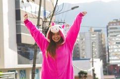关闭穿一套桃红色独角兽服装,用两只手的一个美丽的微笑的少妇在户外在城市 免版税库存照片