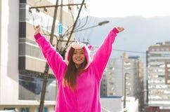 关闭穿一套桃红色独角兽服装,用两只手的一个美丽的微笑的少妇在户外在城市 库存图片