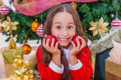 关闭穿一套红色圣诞老人服装和拿着两个圣诞节球在她的手上和按在她的愉快的女孩 免版税库存照片
