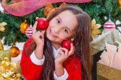 关闭穿一套红色圣诞老人服装和拿着两个圣诞节球在她的手上和按在她的愉快的女孩 库存图片