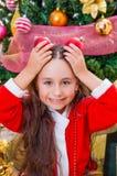 关闭穿一套红色圣诞老人服装和拿着两个圣诞节球在她的手上和摆在她的微笑的女孩 免版税库存照片