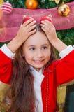 关闭穿一套红色圣诞老人服装和拿着两个圣诞节球在她的手上和摆在她的微笑的女孩 图库摄影