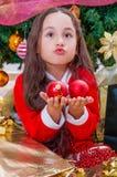 关闭穿一套红色圣诞老人服装和拿着两个圣诞节球在她的手上的愉快的女孩做滑稽的面孔,与a 免版税库存图片