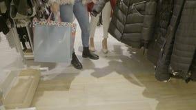 关闭穿偶然服装的妇女腿走和寻找有购物袋的衣裳在他们的手上在购物中心商店- 影视素材