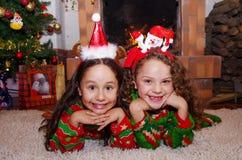 关闭穿圣诞节衣裳的两个美丽的微笑的litle女孩放置在一张白色地毯,有室内的 免版税库存照片