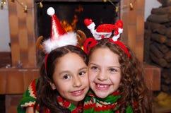 关闭穿圣诞节衣裳的两个美丽的微笑的litle女孩放置在一张白色地毯,有室内的 库存照片
