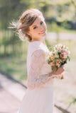 关闭穿有花束的不可思议的美丽的年轻新娘画象典雅的白色礼服在公园 库存照片