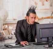 关闭穿着有冠的办公室低劣的工作者衣服,工作在一台计算机,在被弄脏的背景中 库存图片