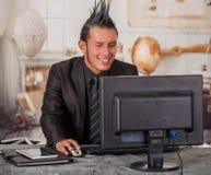 关闭穿着有冠的微笑的办公室低劣的工作者衣服,工作在一台计算机,在被弄脏的背景中 库存图片