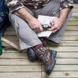 关闭穿迁徙和山的起动的一个人 免版税库存图片
