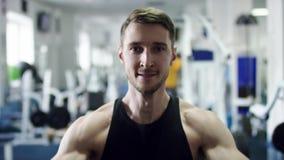 关闭突然上升了一位年轻在健身房的运动员lifiting的哑铃的面孔 股票视频