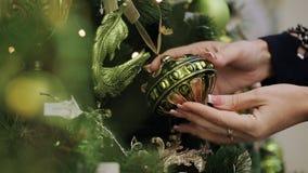关闭突然上升了单独圣诞节玩具的妇女购物 女性手特写镜头采摘圣诞节球并且审查 影视素材