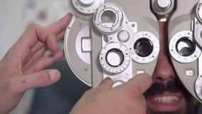 关闭突然上升了白色外套改变的透镜的验光师在phoropter仪器和谈话与有男性的患者 股票录像