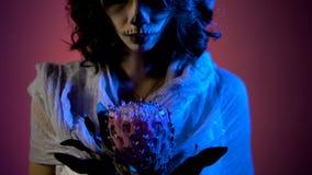 关闭站立与桃红色花的一个女孩的面孔在她的手上和她的与paiting在万圣夜的艺术的面孔 影视素材