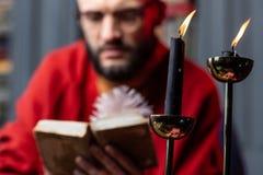 关闭站立在桌上的两个蜡烛在占卜者看书附近 免版税库存图片