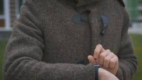 关闭站立在街道的棕色外套的有胡子的深色头发的人 商人设置他的手表  股票视频
