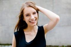 关闭站立对灰色墙壁的观点的年轻微笑的夫人 库存照片