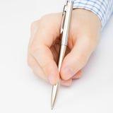 关闭签署或写某事与圆珠笔的一个人的射击 免版税图库摄影