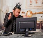 关闭紧张穿着有冠的办公室低劣的工作者衣服,工作在一台计算机,在被弄脏的背景中 库存照片