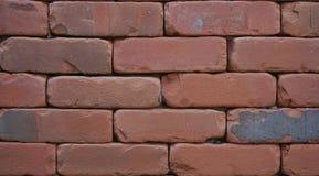 关闭红砖与狭窄的数据块间隔和暗藏的灰浆的墙壁txture 库存图片