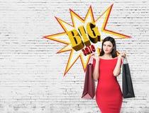 关闭红色礼服的一名妇女有两个购物袋的在大附近 库存图片