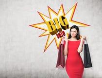 关闭红色礼服的一名妇女有两个购物袋的在大附近 免版税库存照片