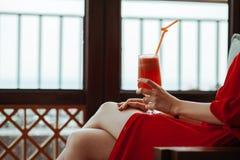 关闭红色礼服的妇女有与橙色秸杆的红色鸡尾酒的在手上 红色礼服喝的美丽的女孩 免版税库存图片