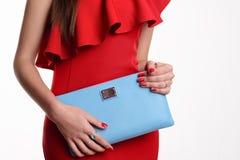 关闭红色礼服的时尚妇女有蓝色提包的 免版税库存图片