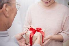 关闭给礼物盒的资深老人和他的女儿的手 免版税库存图片