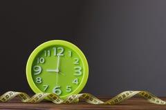 关闭绿色时钟和测量的磁带 免版税库存照片