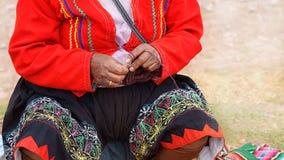 关闭编织在秘鲁 在五颜六色的传统当地秘鲁结束打扮的库斯科,秘鲁妇女编织一张地毯与 免版税库存图片