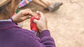 关闭编织在秘鲁 在五颜六色的传统当地秘鲁结束打扮的库斯科,秘鲁妇女编织一张地毯与 免版税库存照片