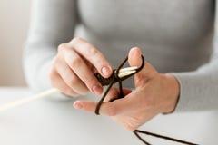 关闭编织与针和毛线的手 免版税库存照片